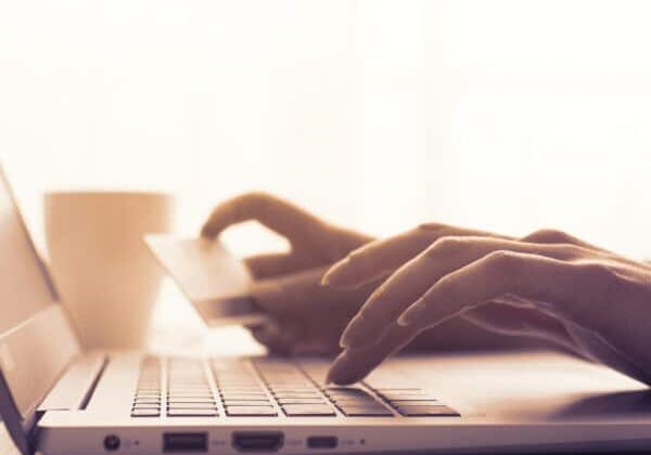 Woman doing online shopping using her laptop and a credit card, hands close up, e-commerce and online banking concept